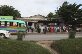 Passengers wait for a dala-dala, the city's informal bus system.